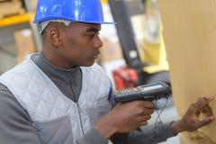 Het systeemarbeider van het pakhuisbeheer met streepjescodescanner stock foto's