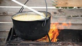 Het tarwegraangewas met vlees wordt voorbereid bij de grill, wordt het bewogen met lepel, close-up stock videobeelden