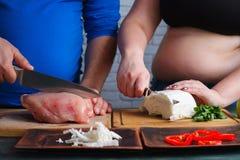 Het te zware voedsel van het paar kokende dieet Het vette man en vrouwen voorbereidingen treffen royalty-vrije stock fotografie