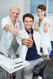 Het team bij tandartsholding beduimelt omhoog Royalty-vrije Stock Foto's