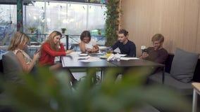 Het team in het coworking na het harde werk besliste een onderbreking en menings sociale netwerken in de telefoon te nemen stock videobeelden