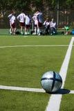 Het team dat van het voetbal op achtergrond rust Stock Fotografie