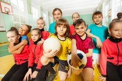 Het team die van het kinderen` s voetbal pret samen in gymnastiek hebben stock fotografie