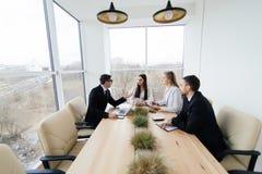 Het team luistert bij vergaderingsleider van project bij conferentielijst royalty-vrije stock afbeelding