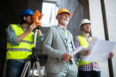 Het team van architecten en de ingenieur in groep op construcitonplaats controleert documenten en bedrijfswerkschema stock foto's