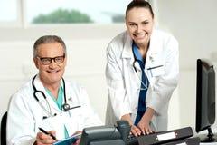 Het team van artsen. Het vrouwelijke hulp typen op toetsenbord Stock Fotografie