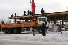 Het team van bouwers die aan de bouw van het gebouw in Novosibirsk, in de winter van gegoten beton werken dat speciaal gebruikt stock afbeeldingen