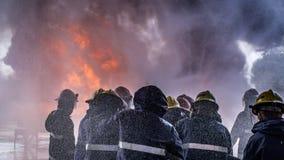 Het team van brandvechters werd opgeleid aan het doven van reusachtige vlam met waterhydrant stock fotografie