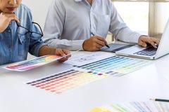 Het team van collega grafische ontwerper die en beeld trekken retoucheren op grafiektablet en kiest de steekproeven van het kleur royalty-vrije stock foto's