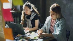 Het team van creatieve ontwerpers werkt in licht bureau samen De donker-haired dame luistert aan muziek en werkt met stock videobeelden