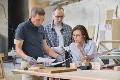 Het team van de arbeiders van de houtbewerkingsworkshop bespreekt De de de de groeps mensen cliënt, ontwerper of ingenieur en arb stock afbeelding