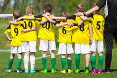 Het team van de jeugdsporten Jonge spelers die zich samen met bus bevinden stock foto's