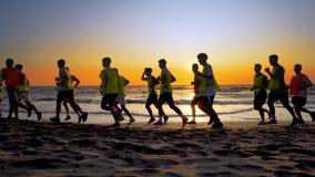 Het team van de voetbalsport is bezig geweest met jogging opleiding op zee bij zonsondergang Stock Afbeelding