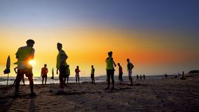 Het team van de voetbalsport klaar voor jogging op het strand bij zonsondergang Royalty-vrije Stock Foto