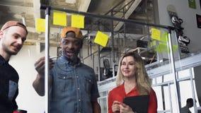 Het team van drie van multi etnische bedrijfsmensen bespreekt en analyserend gegevens van diagram over de glasraad tijdens het we stock footage