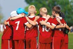 Het team van het kinderenvoetbal De Academie van de kinderenvoetbal Jonge geitjesvoetballers die zich verenigen stock afbeeldingen