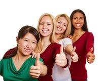 Het team van het multiculturele vrouwen houden beduimelt omhoog stock foto's