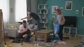 Het team van jonge kerels maakt de woonkamer na de partij schoon stock videobeelden