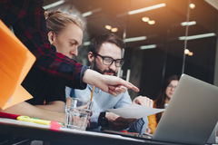 Het team van jonge managers werkt in een modern bureau bij een houten tabl stock afbeeldingen