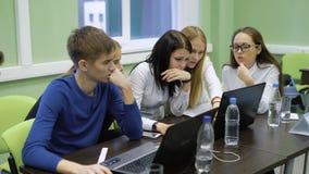 Het team van jonge managers zit samen bij de lijst met laptops en neemt aan de concurrentie in bedrijfsspel deel stock videobeelden