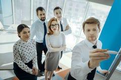Het team van jonge specialisten let op hun werkgever trekt op whiteboard royalty-vrije stock foto's