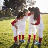 Het team van het meisjeshonkbal in een teamwirwar, die vóór spel motiveren royalty-vrije stock fotografie