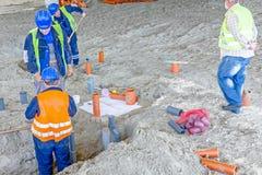 Het team van riggers past aan en assemblage sanitaire pijpen op cons. Royalty-vrije Stock Fotografie
