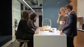 Het team van werknemers eet tijdens middagpauze in bedrijf stock videobeelden