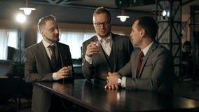 Het team van zakenlieden in pakken spreekt in een een bar en het drinken whisky Het vieren Succes of Succesvol stock videobeelden