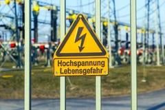 """Het teken bij een elektrische centrale waarschuwt van """"gevaar — hoogspanning"""" Stock Afbeelding"""