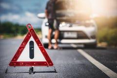 Het teken en de mens van het noodsituatieeinde met gebroken auto Stock Fotografie