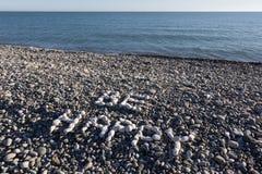 Het teken is Gelukkig van witte kiezelstenen op kiezelsteenstrand dat wordt gemaakt op Royalty-vrije Stock Foto's
