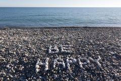 Het teken is Gelukkig van witte kiezelstenen op kiezelsteenstrand dat wordt gemaakt op Royalty-vrije Stock Fotografie