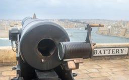 Het teken met Batterij het van letters voorzien op een muur in Hogere Barrakka tuiniert met een zwaar kanon in de voorgrond stock fotografie