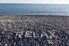 Het teken ontspant gemaakt van witte kiezelstenen op kiezelsteenstrand op Se Royalty-vrije Stock Fotografie