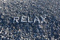 Het teken ontspant gemaakt van witte kiezelstenen op kiezelsteenstrand op Se Stock Foto