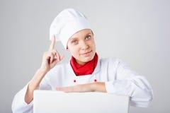 Het Teken van de chef-kok Vrouwenkok die over document tekenaanplakbord kijken Verraste en grappige die uitdrukkingsvrouw op witt Royalty-vrije Stock Foto's