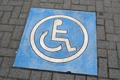 Het teken van de handicap op parkeren Stock Foto