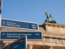 Het Teken van de richting door de Poort van Brandenburg stock afbeeldingen