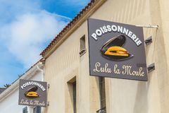 Het teken van een vis winkelt of het wordt geschreven in het Frans - vishandelaar Lulu stock fotografie