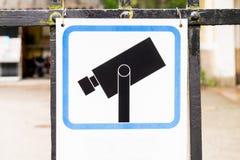 Het teken van het cameratoezicht het hangen op een poort Stock Afbeeldingen