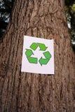 Het teken van het recycling op de boomstam van een boom stock afbeelding