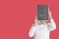 Het teken van het smileygezicht van de mensenholding over rode achtergrond royalty-vrije stock afbeeldingen