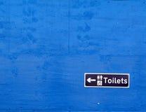Het teken van het toilet op een blauwe muur Stock Afbeeldingen
