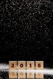 het teken van 2016 meer dan vier houten kubussen die zich op zwart weerspiegelend DE bevinden Royalty-vrije Stock Afbeelding