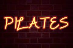 Het teken van het Pilatesneon op bakstenen muurachtergrond Fluorescent T.L.-buisteken op metselwerk Bedrijfsconcept voor de Train Stock Fotografie