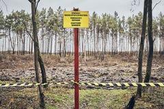 Het teken van het voorzichtigheidsgevaar in een bos wordt gevestigd dat stock foto