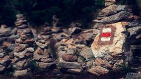 Het tekenteken van de wandelingssleep op een rots in stapel zenstenen die wordt geschilderd Weg belangrijke trog mooi Boheems For royalty-vrije stock afbeeldingen