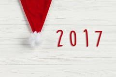 het tekentekst van 2017 op de hoed van Kerstmissanta op witte rustieke houten bac Stock Afbeeldingen