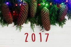 het tekentekst van 2017 op de lichten van de Kerstmisslinger en denneappels op spar Royalty-vrije Stock Afbeelding